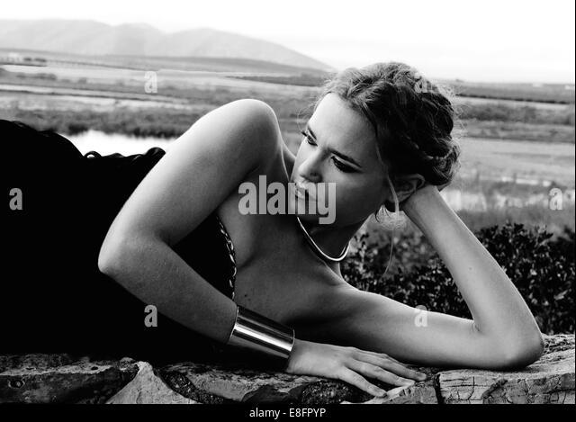 Frau liegt auf Steinmauer Stockbild