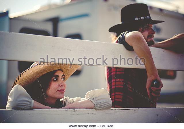 Paar tragen Cowboyhüte stützte sich auf Zaun Stockbild