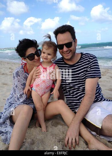 Mutter, Vater und Tochter (18-23 Monate) am Strand Stockbild