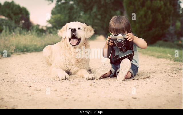 Junge mit seinem Hund zu sitzen und mit alten Kamera fotografieren Stockbild