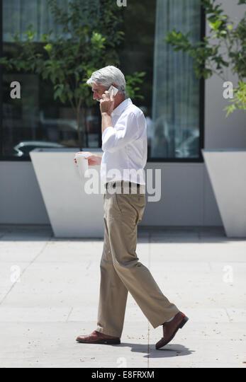 Seitenansicht der Geschäftsmann, die Straße hinunter, während Sie telefonieren mit Handy Stockbild