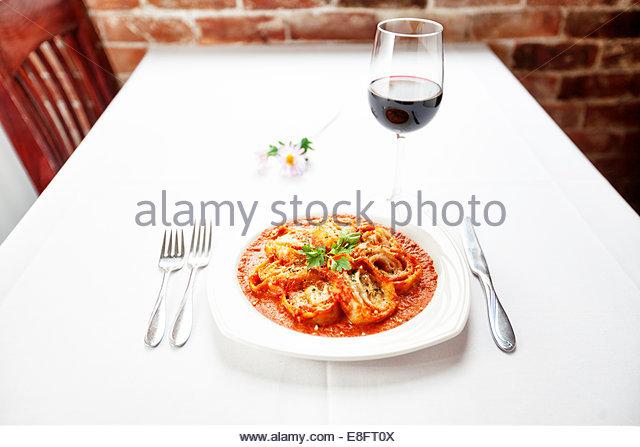 Italienischer Pasta mit Tomatensauce und ein Glas Rotwein zu Rollen Stockbild