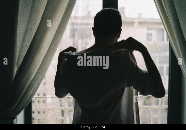Mann auf der Suche durch Fenster Stockbild
