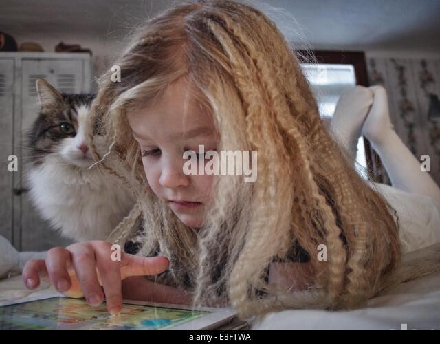 Mädchen mit ihrer Katze mit einem digitalen Tablet auf Bett liegend Stockbild