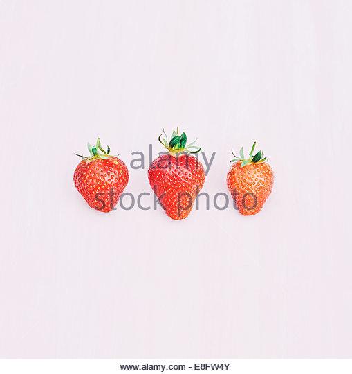 Drei Erdbeeren auf rosa Hintergrund Stockbild