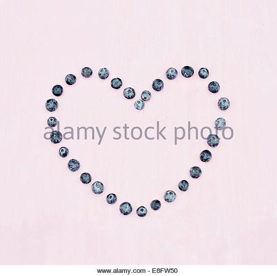 Heidelbeer-Herz auf rosa Hintergrund Stockbild
