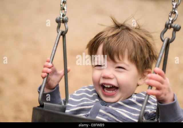 Junge (203) auf Schaukel vor Lachen Stockbild