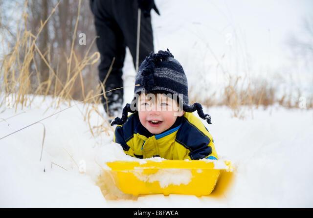 Junge auf Schlitten (2-3 Jahre) Stockbild