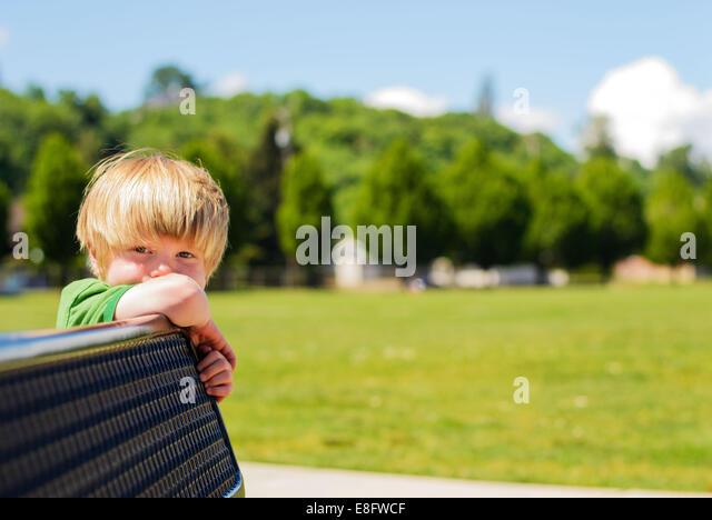 Junge stützte sich auf Bank (4-5 Jahre) Stockbild