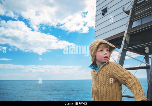 Junge (4-5) auf Leiter wegsehen bei Stockbild