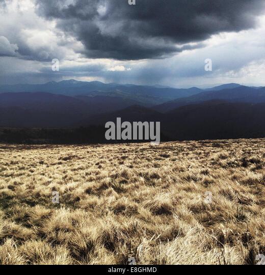 Schwere Wolken über Feld und Berge Stockbild