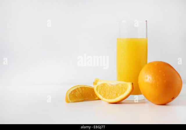 Glas Orangensaft mit frischen Orangen Stockbild