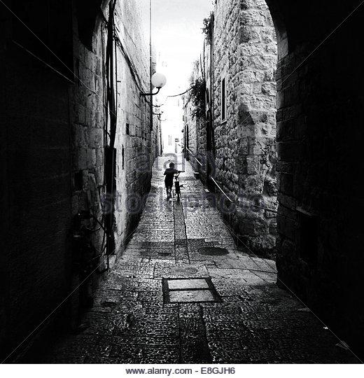 Rückansicht des junge mit Fahrrad auf der Straße Stockbild