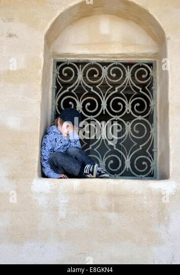 Stockholm, Schweden ein traurig und müde Junge sitzt In einem Fenster Tresor ein Sommertag Stockbild