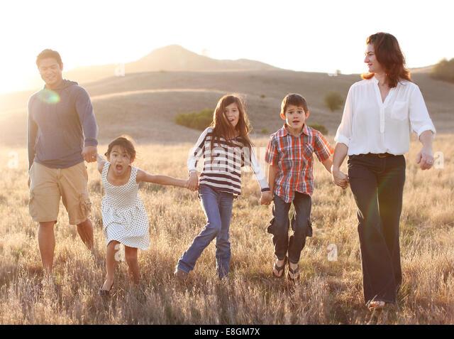 Fünfköpfige Familie Hand in Hand, Wandern in Wiese Stockbild