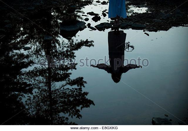 Reflexion der Frau mit ausgestreckten in See Stockbild