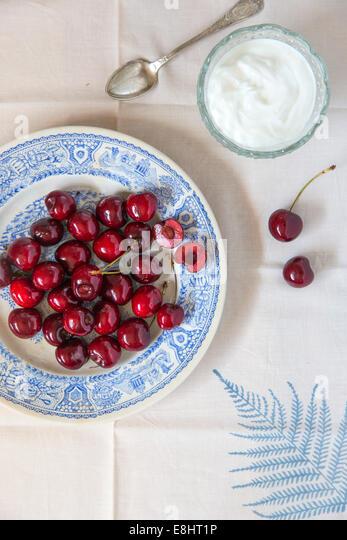 ganze Kirschen auf blaue Keramik-Platte, auf Blatt Leinen und Sahne oder Joghurt in Glasschale mit Vintage Löffel Stockbild