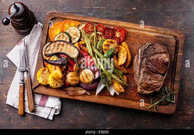 Club-Rindersteak und gegrilltes Gemüse auf Schneidebrett auf dunklem Holz Stockbild