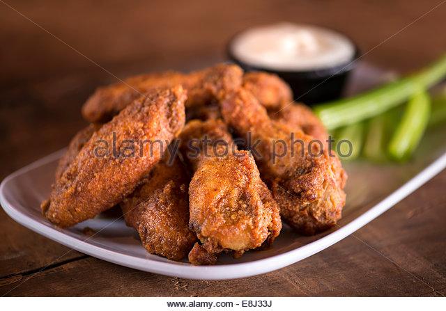 Platte von Chicken Wings mit Ranch und Sellerie auf rustikalen Holzoberfläche. Stockbild