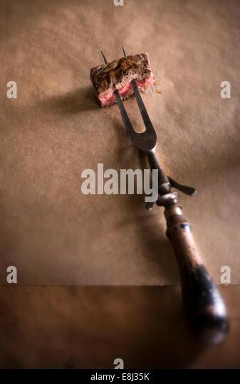 Steak auf antiken Fleischgabel sitzen auf Metzger Papier und rustikale Holz beißen. Stockbild
