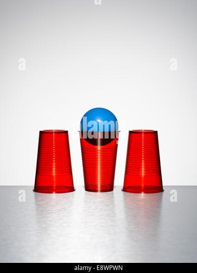 Blaue Kugel in der Mitte der drei rote Tassen Stockbild