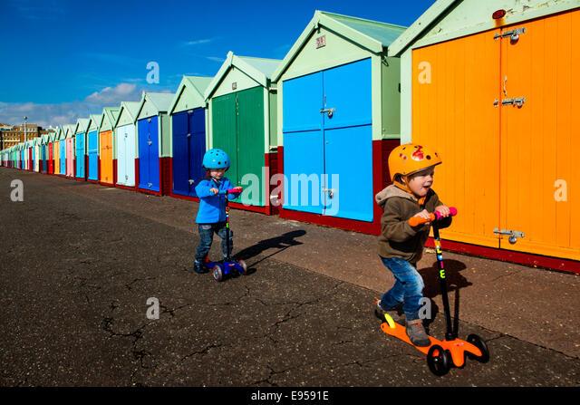 Zwillingen auf Roller im Brighton Strand Hütten Stockbild