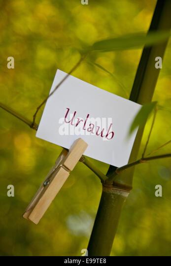 """Das Wort """"Urlaub"""" auf dem Papier in der Natur Stockbild"""