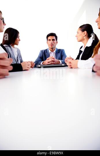Geschäftsleute, die auf einer Sitzung am Tisch sitzen Stockbild