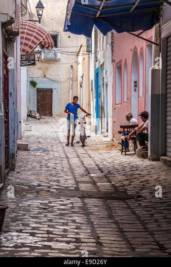 Junger Mann Spaziergänge sein Moped unten einen schmalen gepflasterten Seitenstraße in der Medina von Stockbild