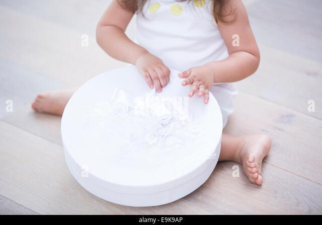 Niedrige Abschnitt von kleinen Mädchen öffnen Geschenkbox im Stock zu Hause Stockbild