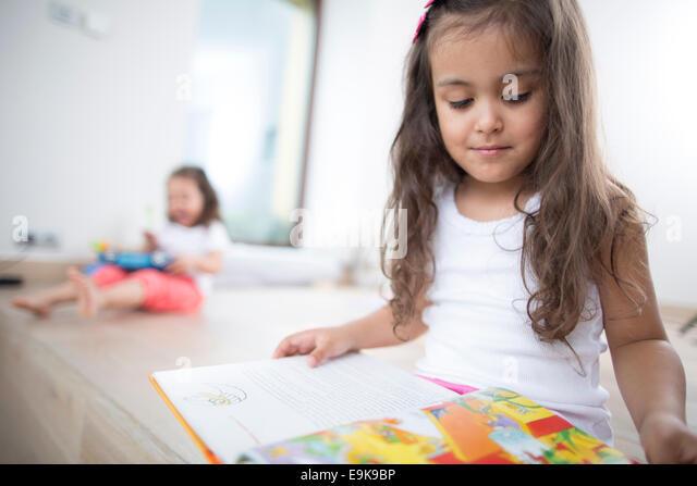 Niedliche Mädchen Buch mit Schwester im Hintergrund zu Hause Stockbild