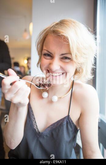 Porträt der glückliche junge Frau Essen Gebäck im café Stockbild
