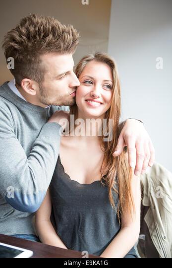Romantischer junger Mann küssen Frau im café Stockbild