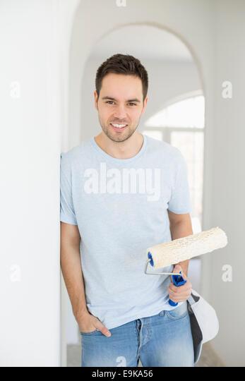 Porträt von gut aussehender Mann mit Farbroller in neues Haus Stockbild