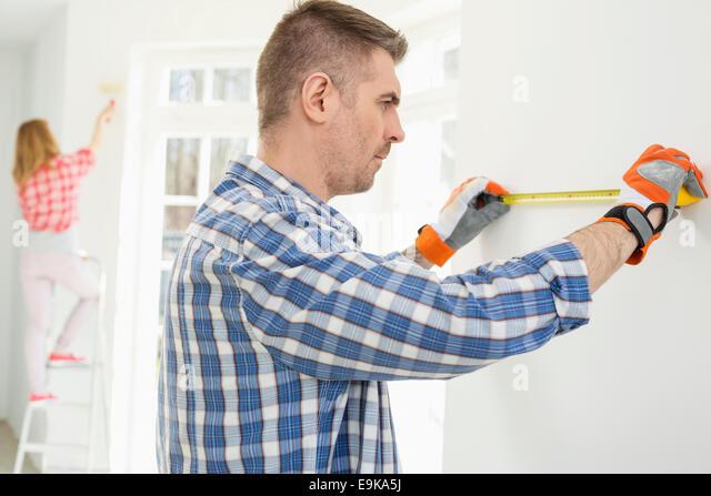 Mann mit Frau malt im Hintergrund Wand messen Stockbild