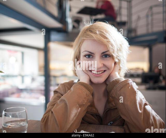 Porträt der schönen jungen Frau lächelnd in café Stockbild