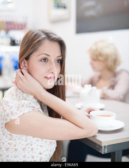 Nachdenkliche junge Frau mit Kaffee im café Stockbild