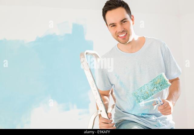 Porträt von glücklicher Mann sein neue Haus malen Stockbild
