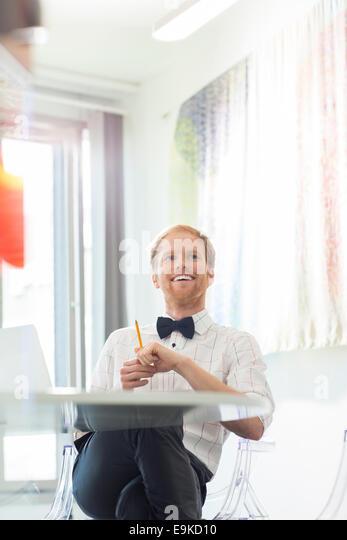 Glücklich Kaufmann in Kreativbüro wegschauen Stockbild