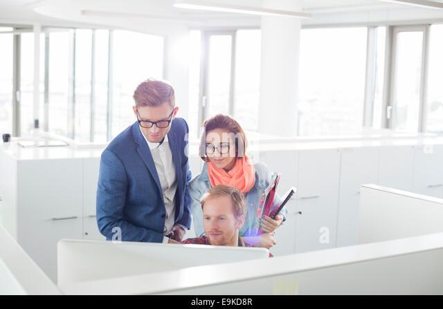 Geschäftsleute, die auf Computer im Kreativbüro Stockbild
