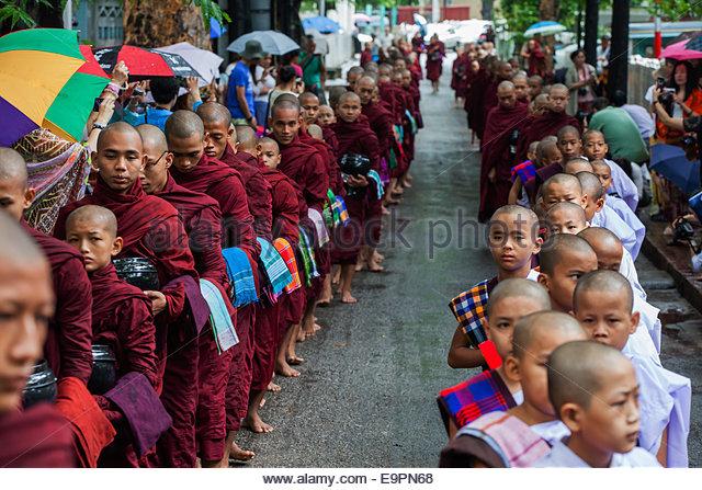 Mönche anstehen für ihre Mahlzeit am Nachmittag am Mahagandayon Kloster, Amarapura, Mandalay. Stockbild