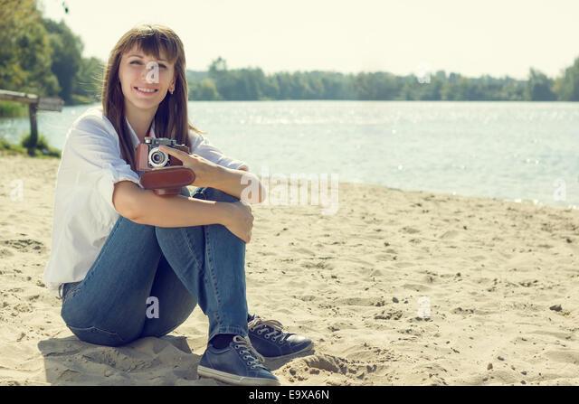 Junge lächelnde Frau mit alten Kamera am Strand ausruhen. Hipster Mädchen posiert in der Nähe von Stockbild