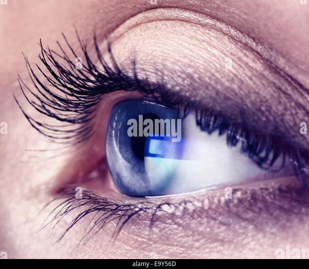 Nahaufnahme von einer jungen Frau Auge mit blauen Computer Bildschirm Reflexion drin Stockbild