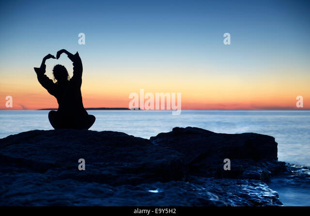 Silhouette einer Frau, die allein ein Ufer bei Sonnenuntergang mit ihren Händen zu erhöhen, in Form einer Stockbild