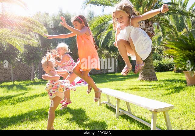 5 energetische Mädchen springen von Gartenbank Stockbild