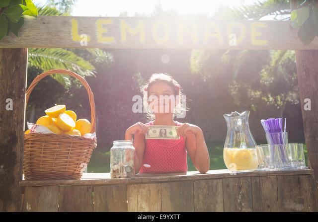 Porträt von stolz Mädchen auf Limonadenstand hochhalten einer Dollarnote Stockbild