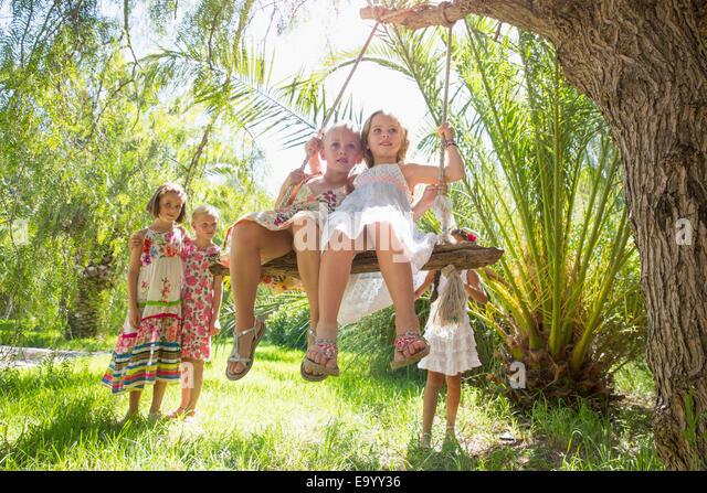 Fünf Mädchen spielen mit Baum-Schaukel im Garten Stockbild