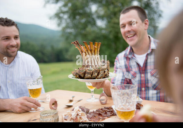 Kleine Gruppe von Erwachsenen Essen im Freien genießen Stockbild