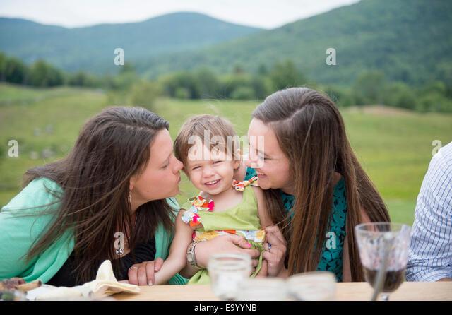 Babymädchen sitzen zwischen zwei jungen Frauen Stockbild