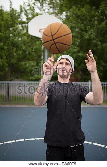 Junger Mann Ausgleich Basketball am finger Stockbild